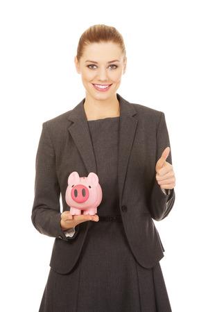 coinbank: Business woman with piggybank and thumbs up.