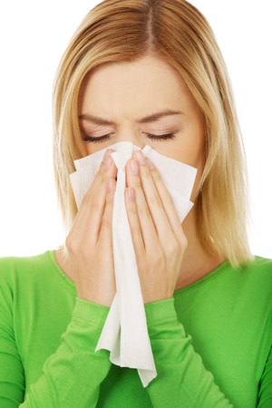running nose: Ill woman sneezing to tissue.