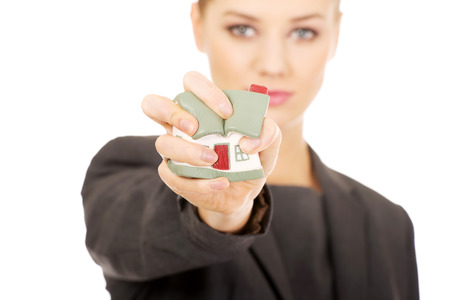 aggresive: Aggresive businesswoman crushing small house. Stock Photo