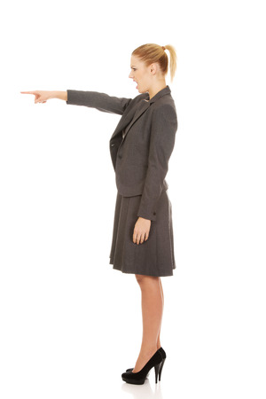aggresive: Angry young businesswoman pointing aside. Stock Photo