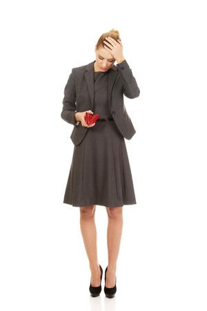empty wallet: Shocked woman looking into her empty wallet.