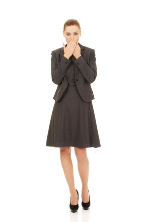 covering mouth: Young businesswoman covering mouth with hands.