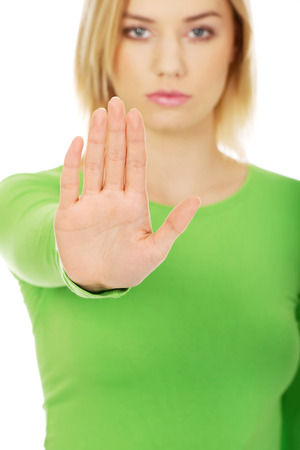 disallow: Young caucasian woman with stop gesture.