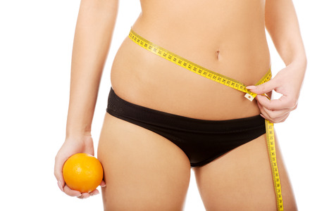 are slim: Slim woman with apple measuring her waist.