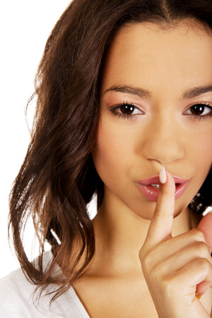 noiseless: African woman making a hush gesture. Stock Photo