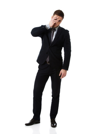 embarassed: Handsome worried businessman touching his forehead. Stock Photo