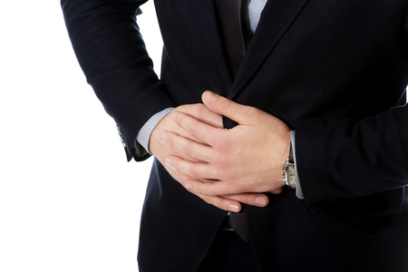 achy: Young handsome businessman suffering from stomach pain. Stock Photo