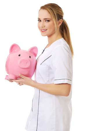 Young beautiful female doctor holding a piggybank. photo