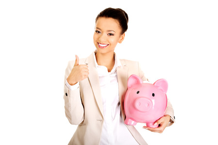 coinbank: African businesswoman with piggybank and thumbs up. Stock Photo
