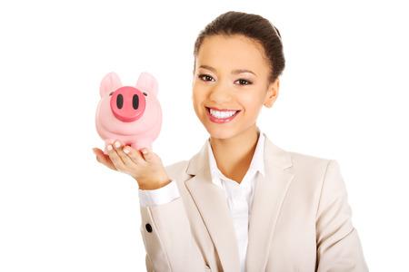 coinbank: African business woman with a piggybank. Stock Photo