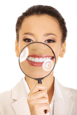 Businesswoman with magnyfying glass on teeth. photo