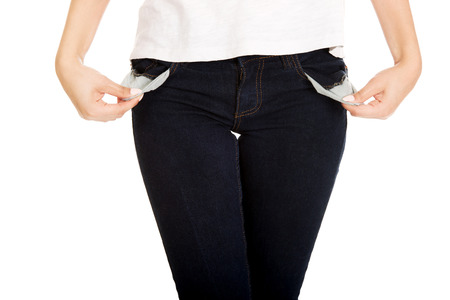 moneyless: Young woman showing empty pockets.