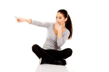cross legged: Shocked woman sitting cross legged pointing aside. Stock Photo