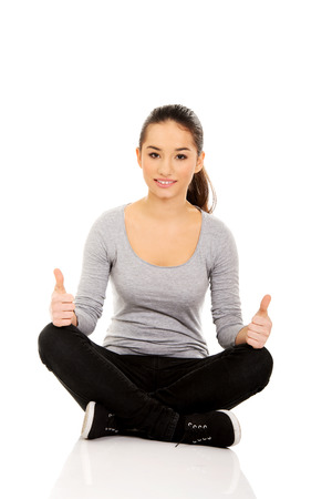 indian style sitting: Young woman sitting cross legged with thumbs up.