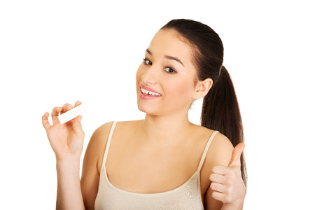 Woman with pregnancy test and thumbs up. photo