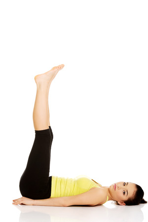 Fitness woman with her legs up practising yoga. photo