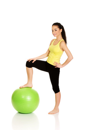 pilates studio: Young fitness woman relaxing with pilates ball. Stock Photo