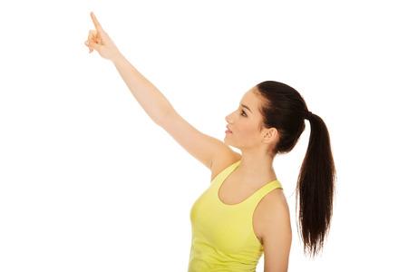 ropa deportiva: Hermosa mujer atlética en ropa deportiva que apunta hacia arriba.