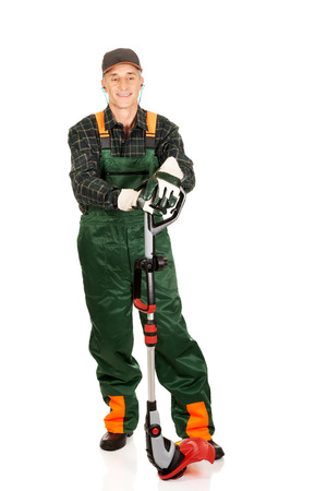 protectors: Experienced gardener with trimmer and ear protectors