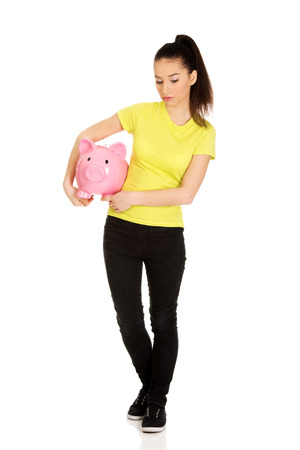 Sad teenage woman holding piggybank. photo