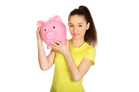 Happy teenage woman holding piggybank. photo