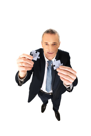 Smart mature man trying to connect puzzle pieces. photo