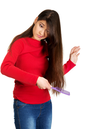 tangled: Painful woman combing her tangled hair. Stock Photo