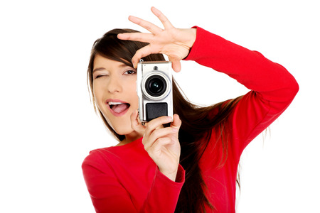 Young woman taking a photo with a camera. photo