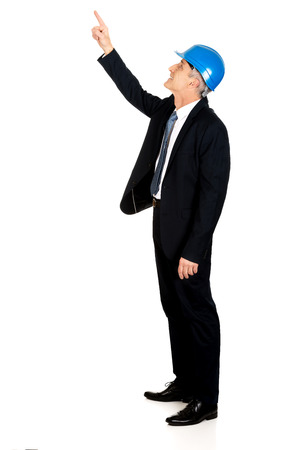 Mature businessman engineer with hard hat pointing up. photo