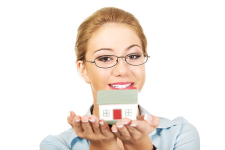 Happy businesswoman presenting a house model. photo
