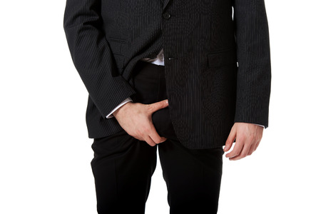 penis: Young businessman holding his crotch because of pain. Stock Photo