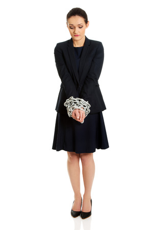 cuffs: Arrested businesswoman with handcuffs around hands.