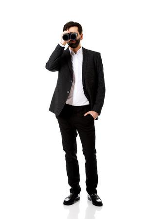 Young handsome businessman looking through binoculars. photo