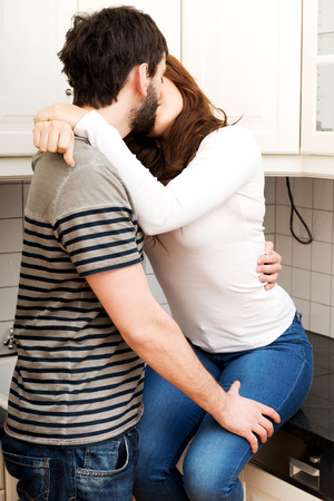 legs around: Young beautiful couple kissing in the kitchen. Stock Photo