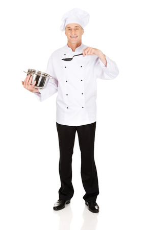 stockpot: Restaurant chef holding steel pot and spoon