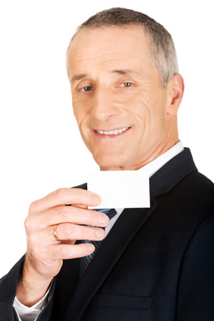 cardkey: Mature businessman showing a blank identity name card. Stock Photo