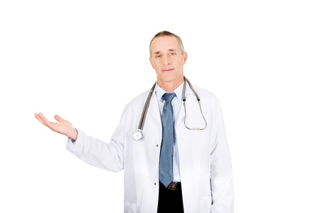 doctor holding gift: Mature male doctor holding copyspace. Stock Photo