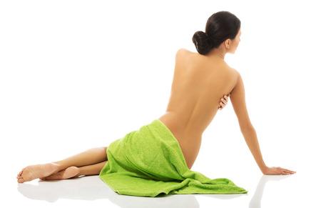 mujer desnuda de espalda: Mujer del balneario sentado envuelto en una toalla de espaldas a la cámara.