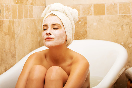 Woman sitting in bath with face mask, wearing towel on head.