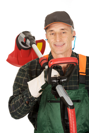 trimmer: Experienced gardener with trimmer and ear protectors