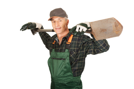 dibble: Smiling experienced gardener with a spade on shoulders