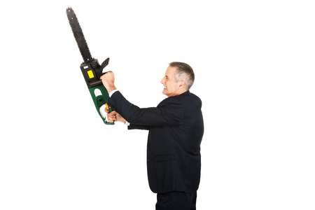 furious: Furious mature businessman with chainsaw.
