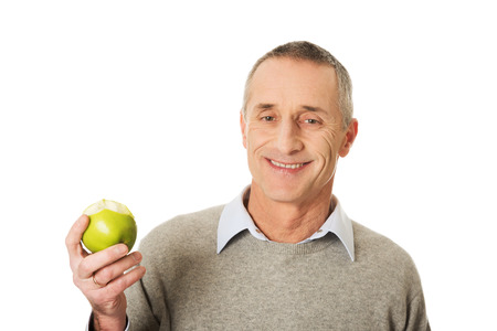 only seniors: Smiling mature man with an apple. Stock Photo