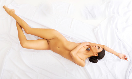 above head: Spa nude woman lying down on a bedsheet. Stock Photo