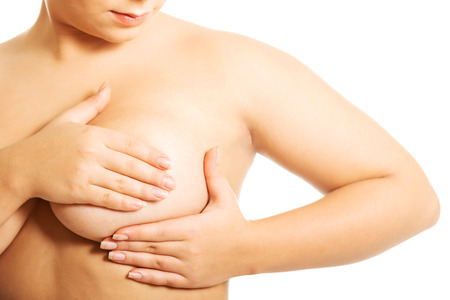 nude breasts: Overweight woman examining her breast. Stock Photo