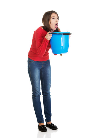 Young sick woman vomiting to bucket.