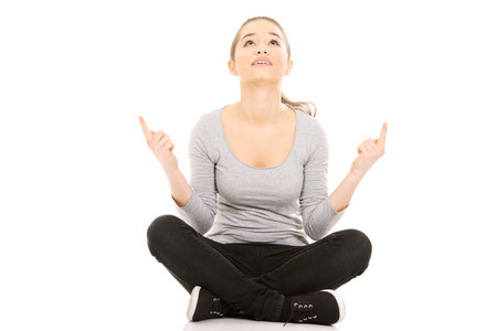 Young woman sitting cross legged pointing up.