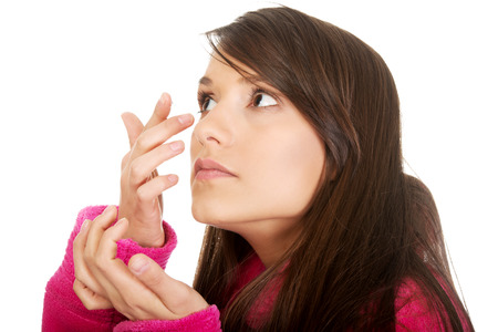 wearer: Woman in bathrobe putting contact lens in her eye. Stock Photo
