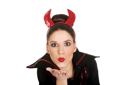 hot kiss: Beautiful woman in devil carnival costume blowing a kiss.