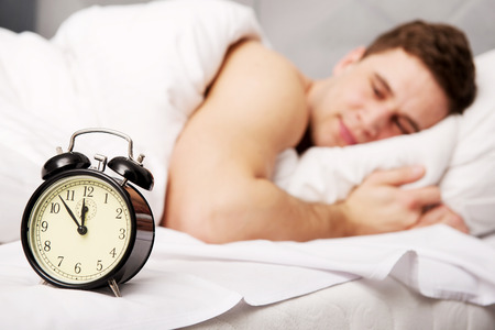 late 20s: Man lying on the bed with alarm clock. Stock Photo